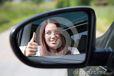 Happy driver showing thumbs up in the mirror