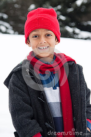 Happy East Indian boy playing in the snow