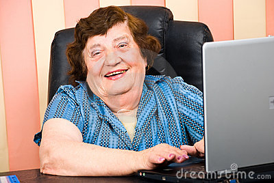Happy elderly business woman using laptop