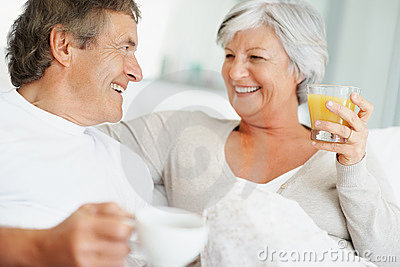 Happy elderly couple enjoying beverages together