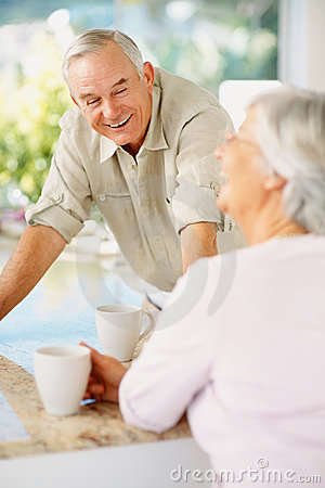 Happy elderly couple enjoying coffee at table