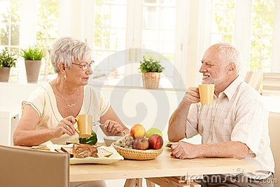 Happy elderly couple having breakfast
