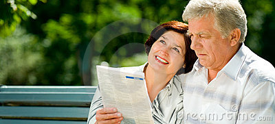 Happy elderly couple reading