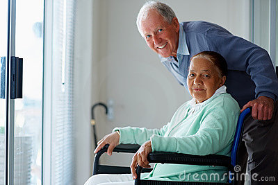 Happy elderly couple , woman on a wheel chair