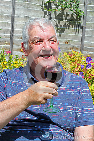 Happy elderly man drinking a glass of wine.