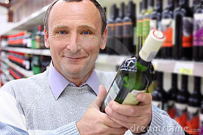 Happy elderly man with wine bottle