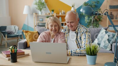 Happy elderly people using laptop to make video call talking gesturing indoors. Happy elderly people are using laptop to make video call talking gesturing stock video
