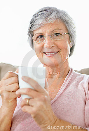Happy elderly woman drinking coffee on white