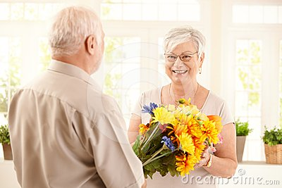 Happy elderly woman getting flowers