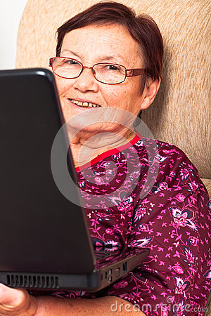 Happy elderly woman with laptop