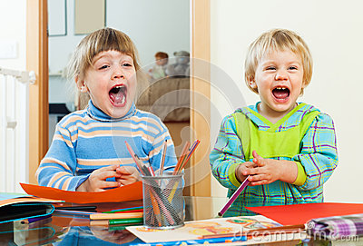 Happy emotional children playing with pencils Stock Photo