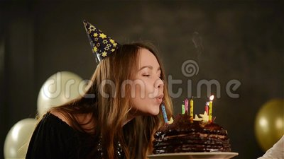 Happy Emotional Girl Blows out Candles During Celebration Her Birthday and Applauds. Close up Portrait of Young Lady. With Chocolate Cake, HD stock video footage