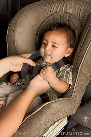 Happy ethnic Asian baby boy child put in carseat