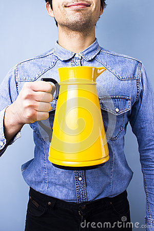 Happy ethnic man holding a jug