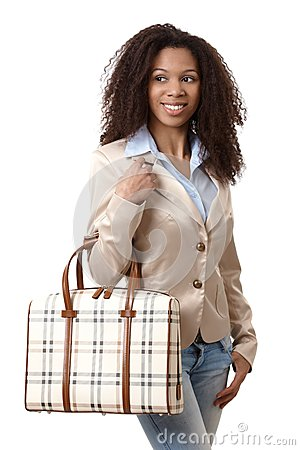 Happy ethnic woman holding handbag