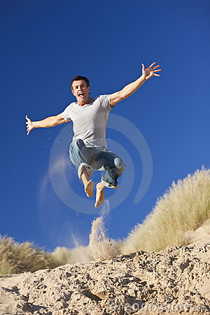 Happy Excited Young Man Jumping On A Beach