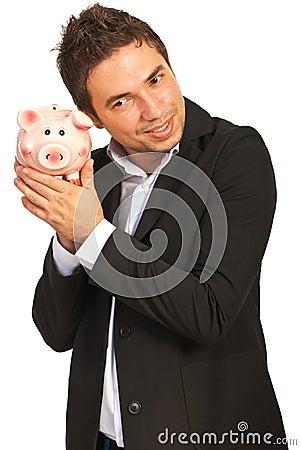 Happy executive listen to piggy bank