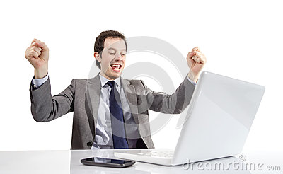 Happy executive man looking a laptop computer with arms raised i