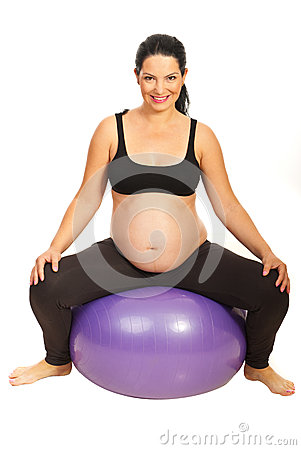 Happy expectant woman on pilates ball