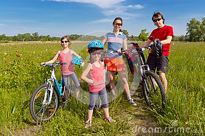 Happy family on bikes, cycling outdoors