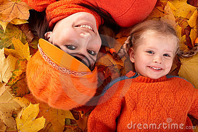 Happy family with child on autumn orange leaf.