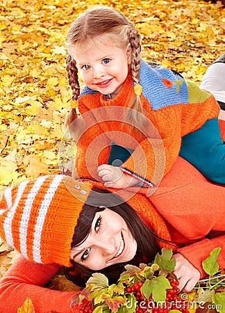 Happy family with child on autumn orange leaves.