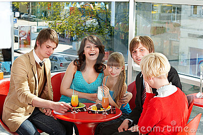 Happy family with child in cafe.