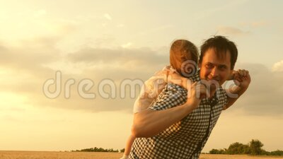 Happy family and childhood concept. daughter on father`s shoulders. happy child and father are playing in a field of. Happy family and childhood concept stock footage