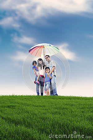 Happy family with colorful umbrella in meadow
