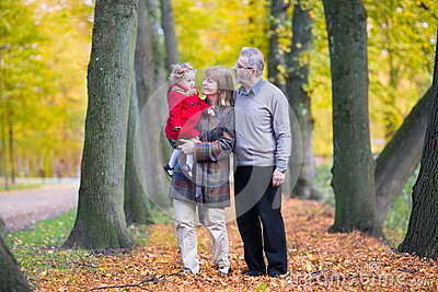 Happy family with cute toddler girl walking in park