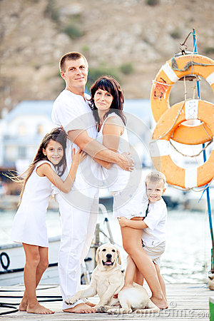 Happy family with dog on berth in summer