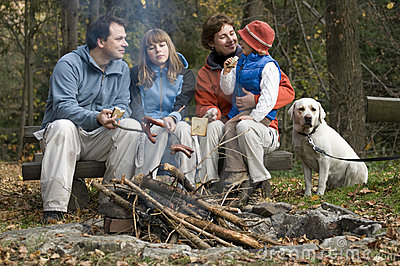 Happy family with dog near campfire