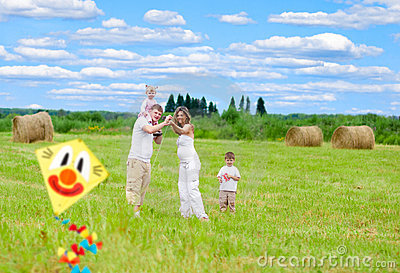 Happy family fly kite summertime