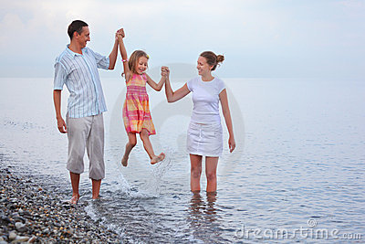 Happy family with girl on beach, parents lift girl