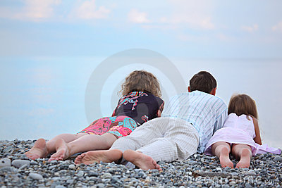 Happy family with girl lying on beach, lying back