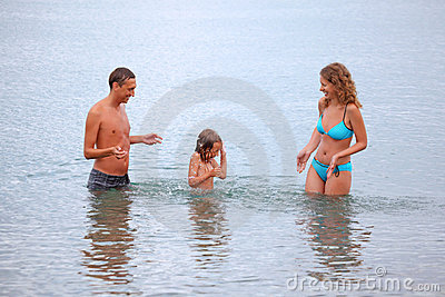 Happy family with girl splashes water hands