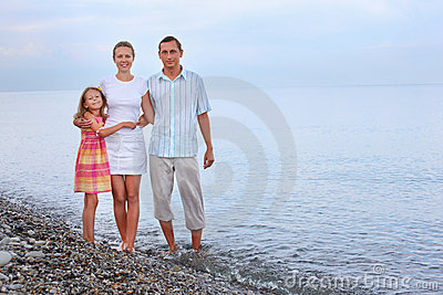 Happy family with girl standing on beach