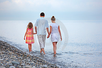 Happy family with girl walk on beach in evening