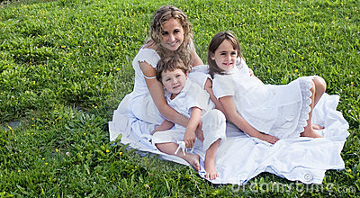 Happy family on the grass with white dresses