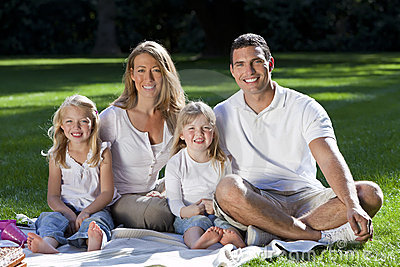 Happy Family Having Picnic In A Park