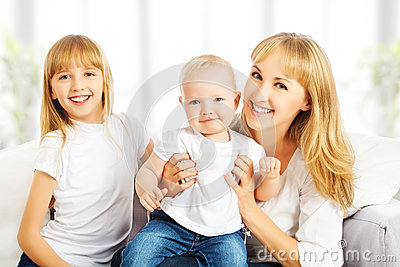 Happy family at home on couch. Mother and daughter and son