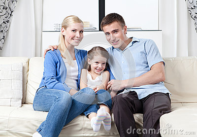Happy family hug each other on the sofa