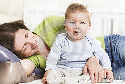 Happy family: Joyous mother and baby boy sitting in bed.