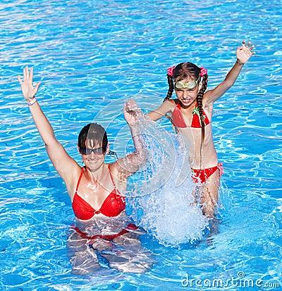 Happy family learn child swim in swimming pool.