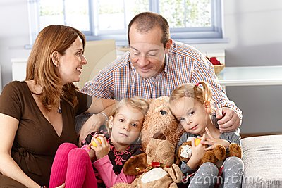 Happy family with little daughters at home