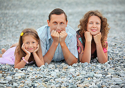 Happy family lying on stony beach, focus on father