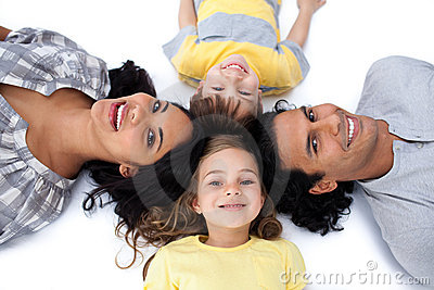 Happy family lying together on the floor in circle