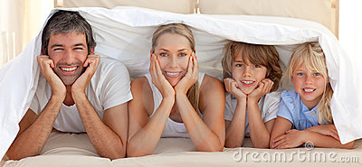 Happy family lying under a blanket