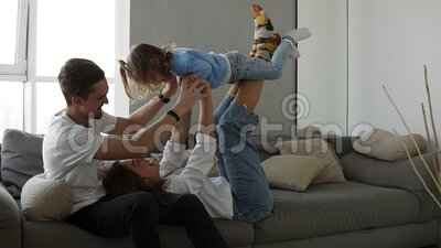 Happy Family Mom And Dad Having Fun With Little Girl On Cozy Home