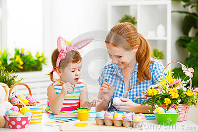 Happy family mother and child girl paints eggs for Easter Stock Photo